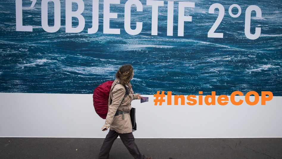 """Picture : a woman walks in front of an """"Objectif 2°C"""" sign"""